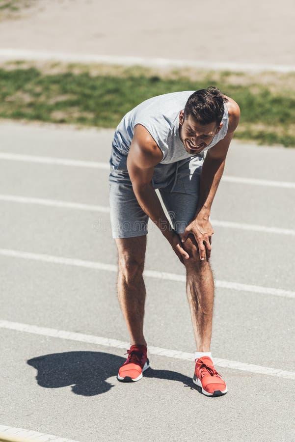 le jeune sportif de souffrance reçoivent la blessure au genou photo stock