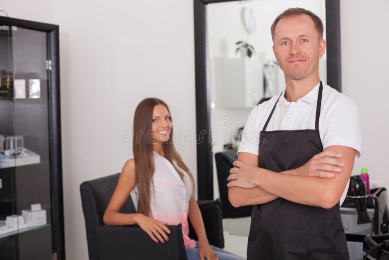 Le jeune styliste en coiffure gai sert son client image stock