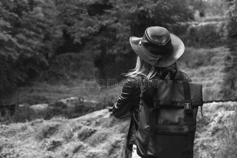 Le jeune touriste féminin avec le chapeau de sac à dos et de cowboy regardant la rivière a enlevé le pont, le croisement était im images stock