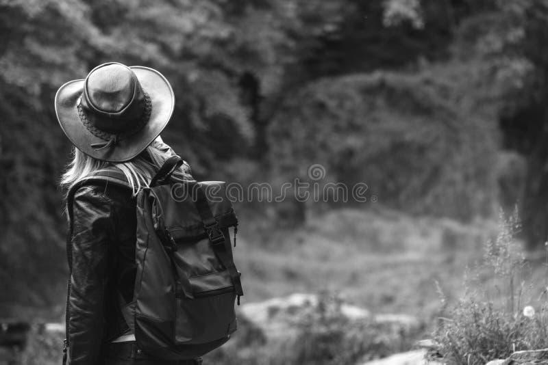 Le jeune touriste féminin avec le chapeau de sac à dos et de cowboy regardant la rivière a enlevé le pont, le croisement était im image stock
