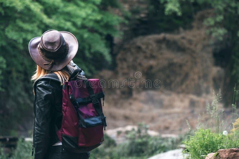 Le jeune touriste féminin européen avec le chapeau de sac à dos et de cowboy regardant la rivière a enlevé le pont, le croisement image stock