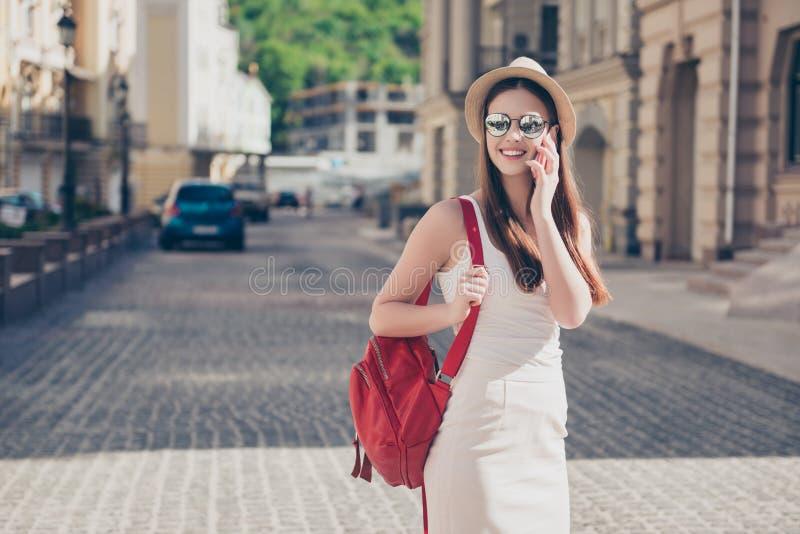 Le jeune touriste mignon parle au téléphone dehors, utilisant le chapeau, images libres de droits
