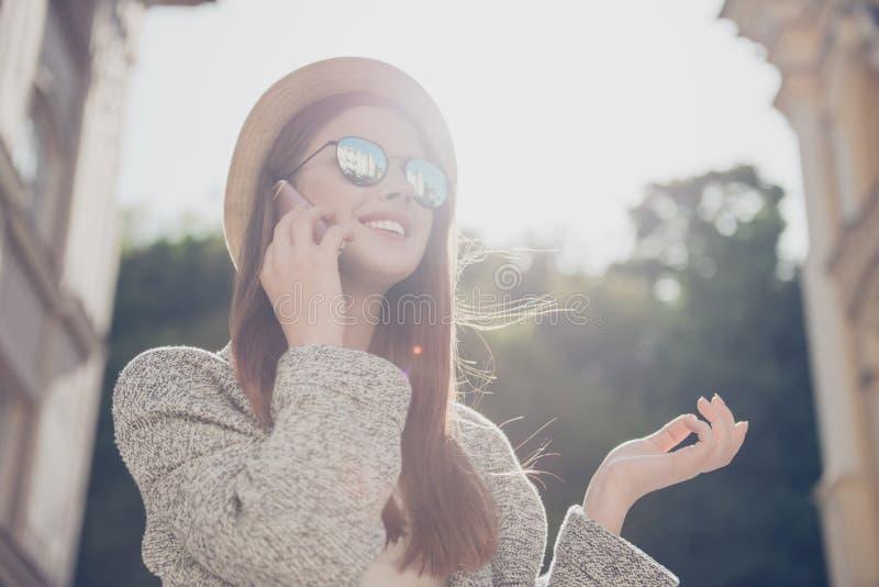 Le jeune touriste mignon parle au téléphone dehors, utilisant le chapeau, photo libre de droits