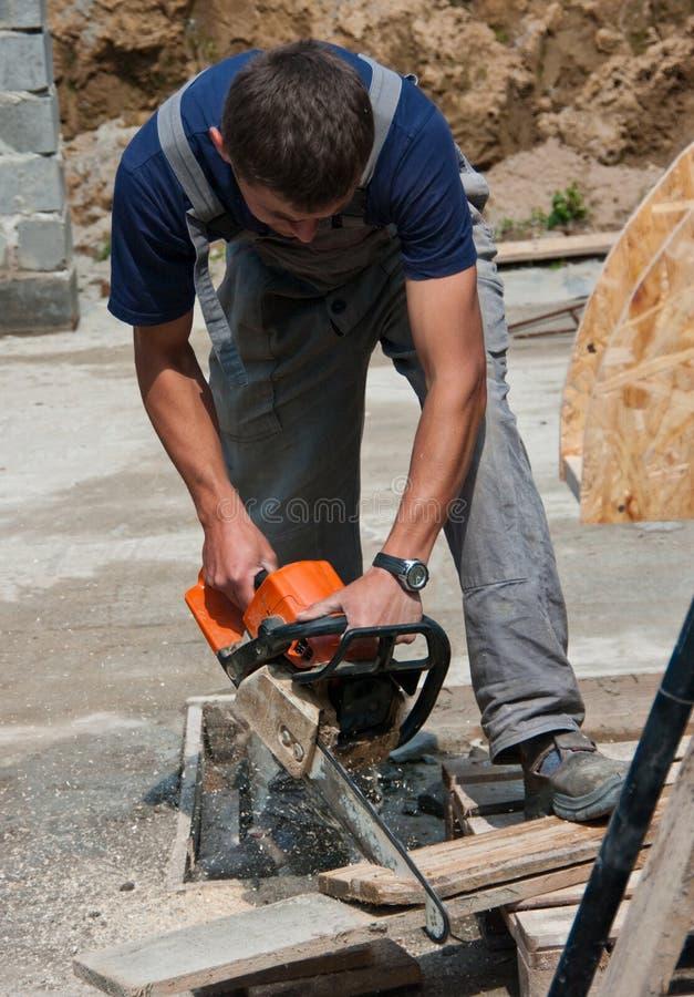 Le jeune travailleur avec a vu image stock