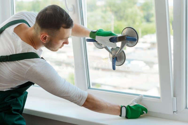 Le jeune travailleur répare la fenêtre photographie stock libre de droits