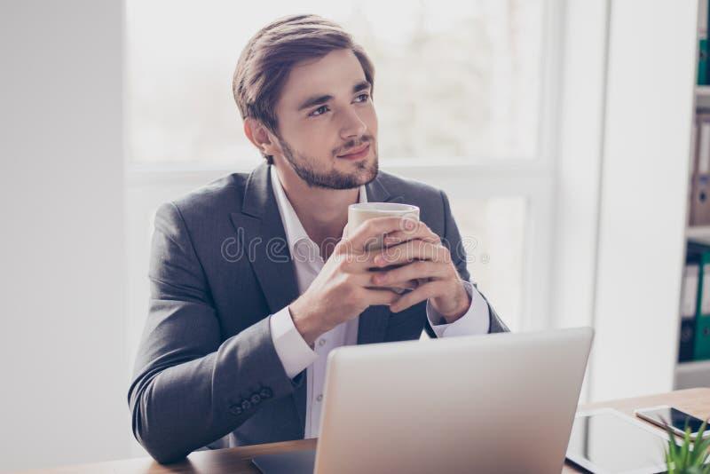 Le jeune travailleur rêvant pense devant l'ordinateur portable au pla de travail photos stock