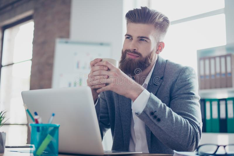 Le jeune travailleur rêvant pense devant l'ordinateur portable au pla de travail photo stock