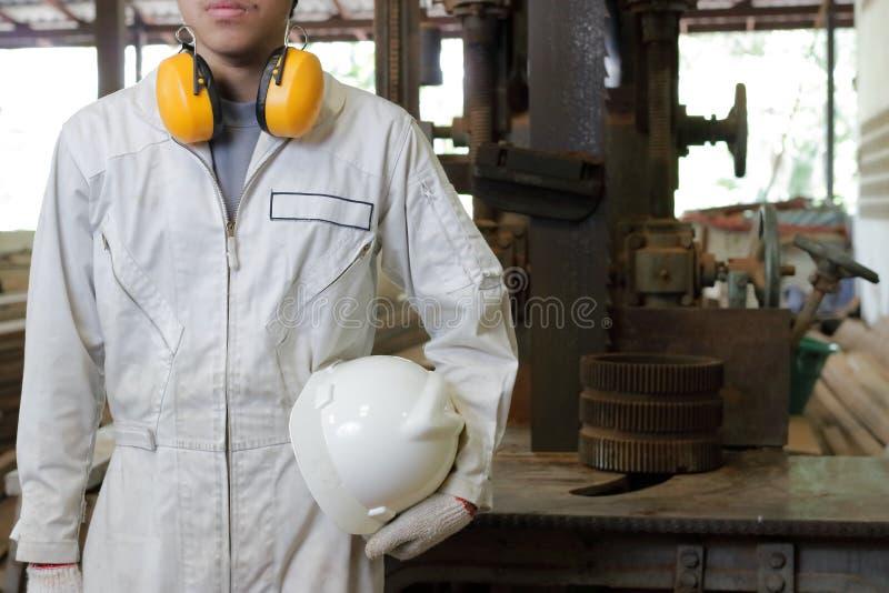 Le jeune travailleur sûr avec l'uniforme de sécurité se tenant dans l'usine avec les scies de bande verticales usinent le fond image libre de droits