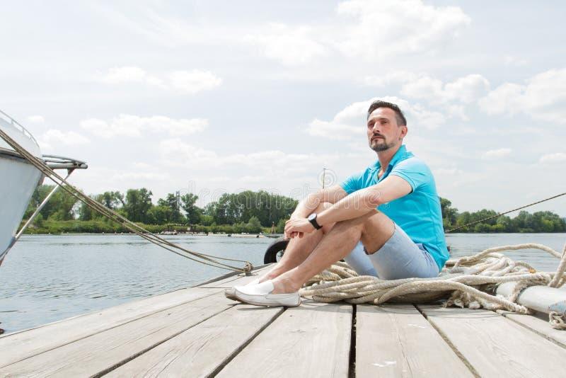 Le jeune type attirant s'assied dans le polo bleu sur le pilier près du yacht homme bel de touristes souri détendant et apprécian photo libre de droits