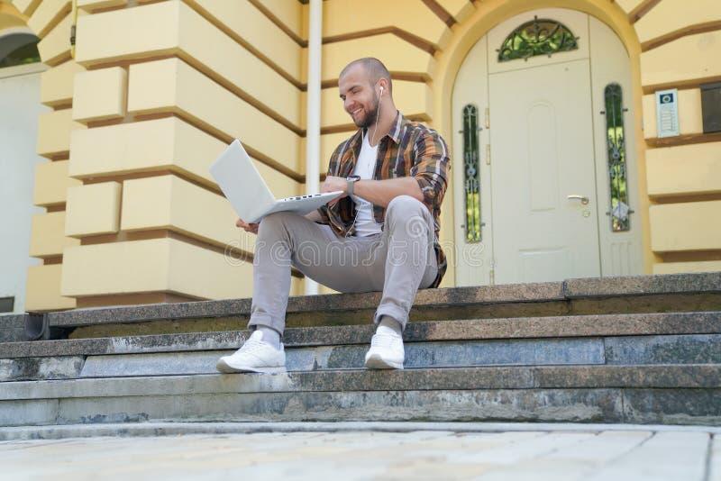 Le jeune type barbu audacieux beau s'assied dehors sur des escaliers devant sa maison travaillant sur l'ordinateur portable il so images libres de droits