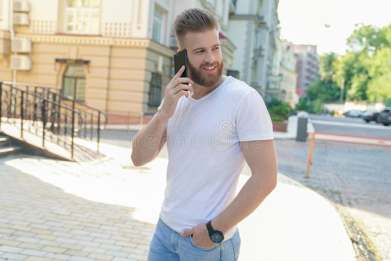 Le jeune type barbu beau s'assied dehors devant sa maison parlant sur le téléphone et le sourire photo stock