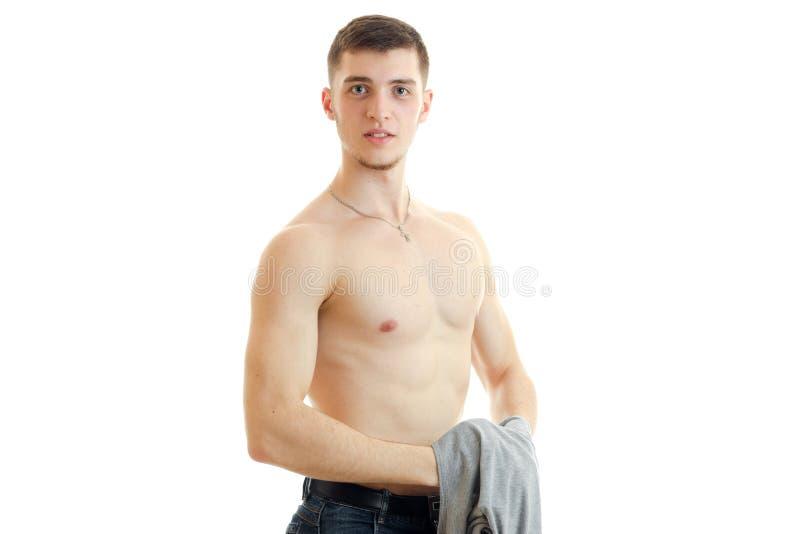 Le jeune type beau se tient avec le torse dénudé tenant Mike et regarde dans un appareil-photo photo stock