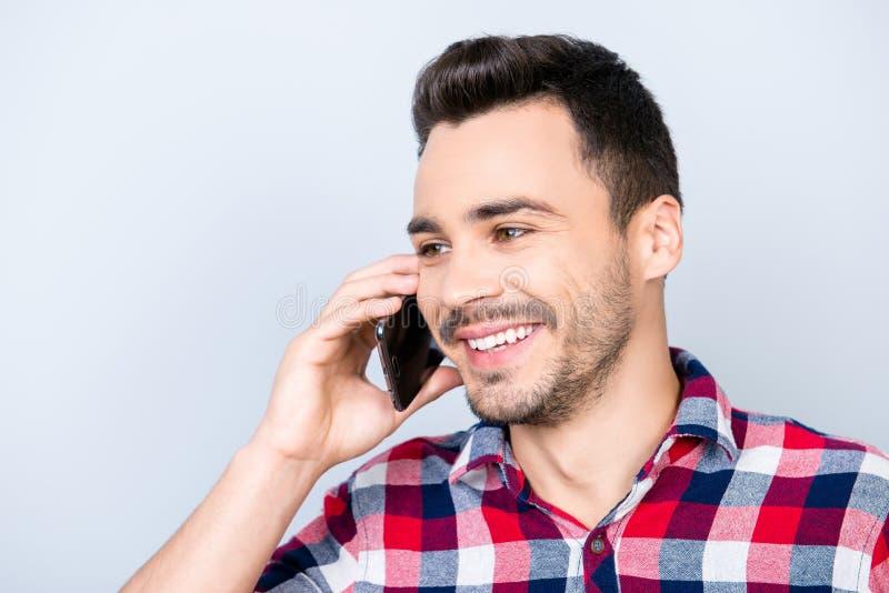 Le jeune type châtain beau enthousiaste parle à son téléphone intelligent images libres de droits