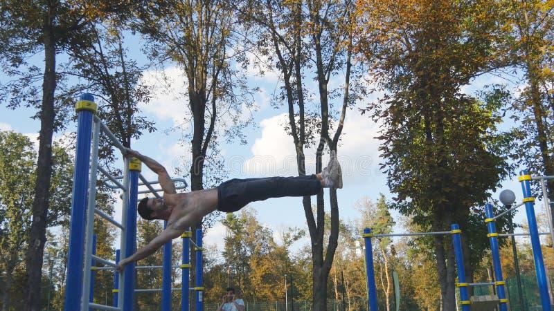 Le jeune type démontre le drapeau humain Homme sportif faisant des éléments de gymnastique sur la barre horizontale en parc de vi photos libres de droits