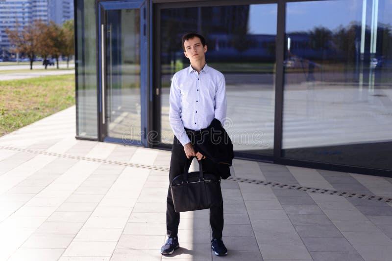Le jeune type d'homme d'affaires se tient près du bâtiment avec de grandes fenêtres photo libre de droits