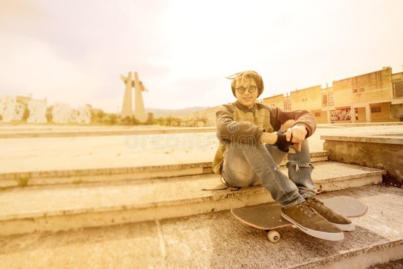 Le jeune type de rasta extérieur sur le patin avec un filtre chaud s'est appliqué image stock