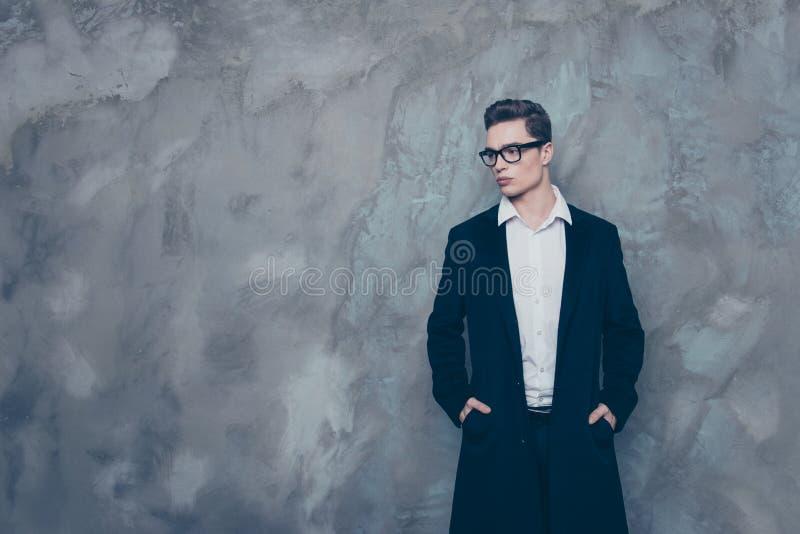Le jeune type réussi beau dans les lunettes et le manteau noir se tiennent photographie stock libre de droits