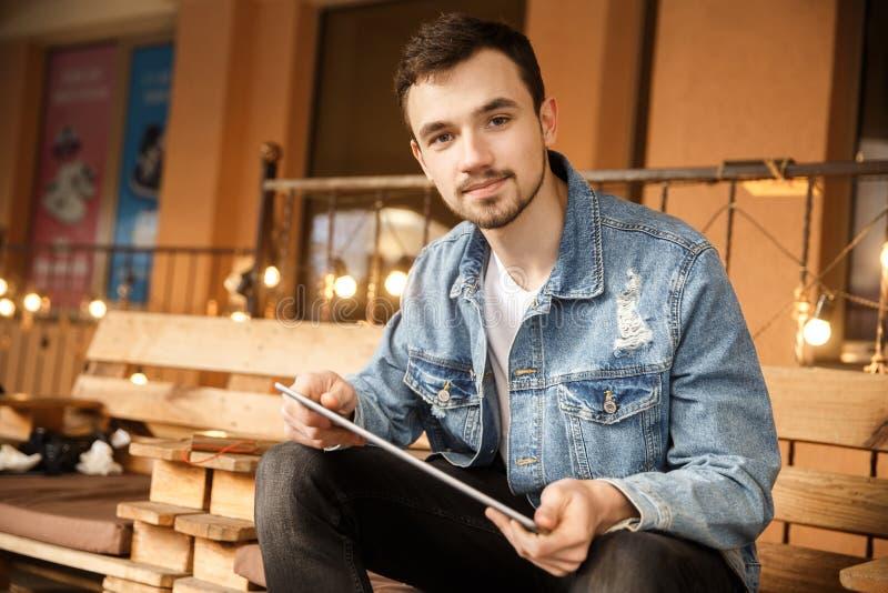 Le jeune type satisfait regarde la caméra tout en tenant son comprimé Il s'assied sur la terrasse de café photo libre de droits