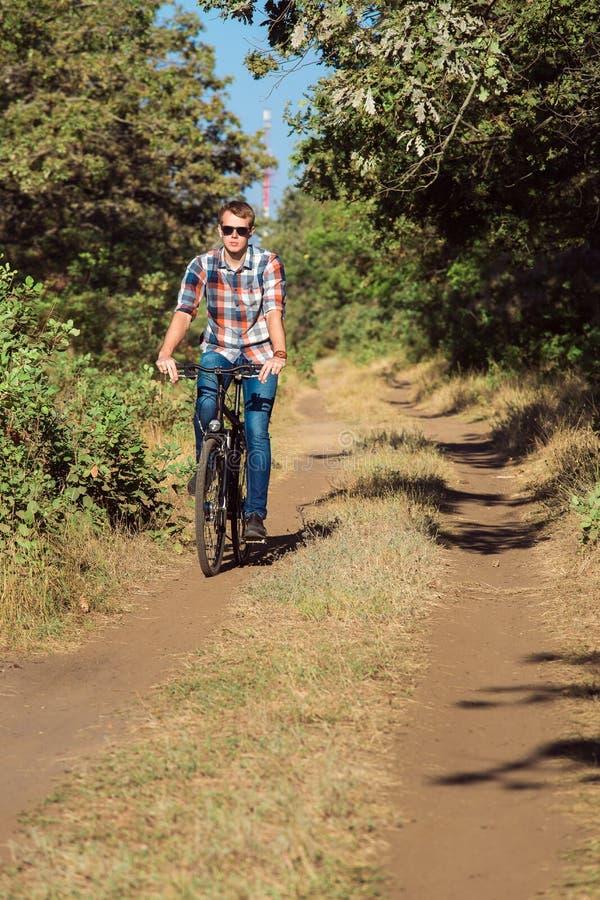 Le jeune type sur la forêt avec la bicyclette photographie stock libre de droits