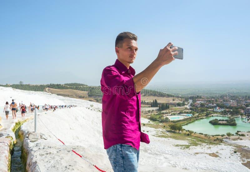 Le jeune type, touriste, prend des photos avec sa PA de vue de téléphone portable photographie stock libre de droits