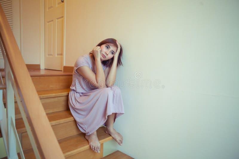Le jeune womanl asiatique seul se repose sur des escaliers images libres de droits
