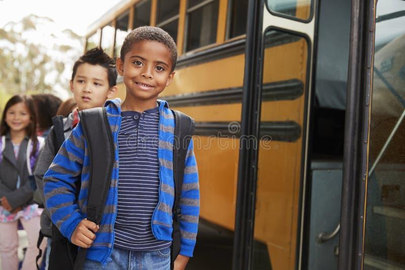 Le jeunes écolier et amis noirs attendent pour monter dans l'autobus scolaire images stock