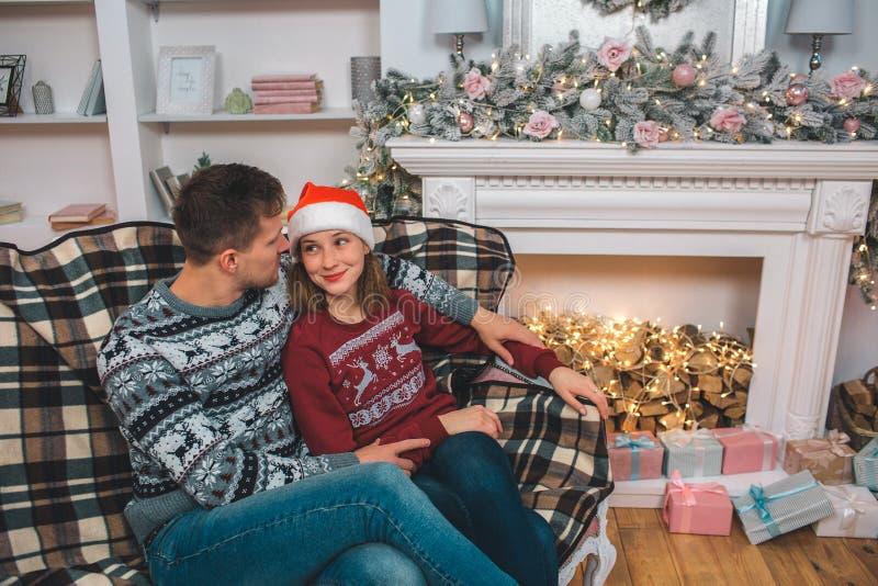 Le jeunes amn et femme se reposent sur le sofa et l'étreinte et regardent l'un l'autre La femme utilise le chapeau de Noël Ils se images libres de droits