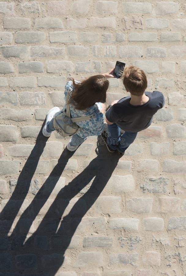 Le jeunes garçon et fille regardent le téléphone portable n la rue photos stock