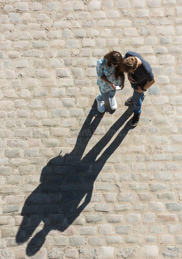 Le jeunes garçon et fille regardent le téléphone portable n la rue photo stock