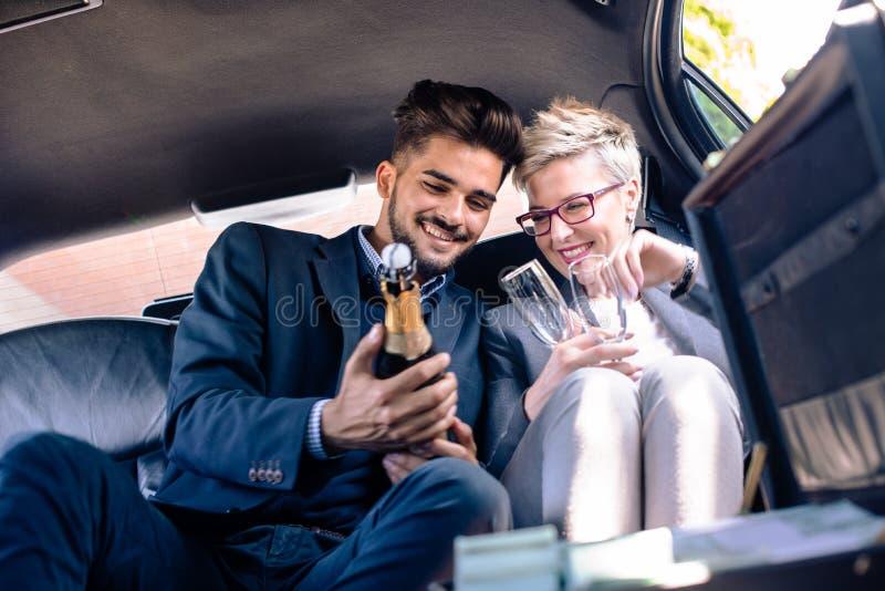 Le jeunes homme et femme d'affaires ouvrent le champagne dans la limousine image libre de droits