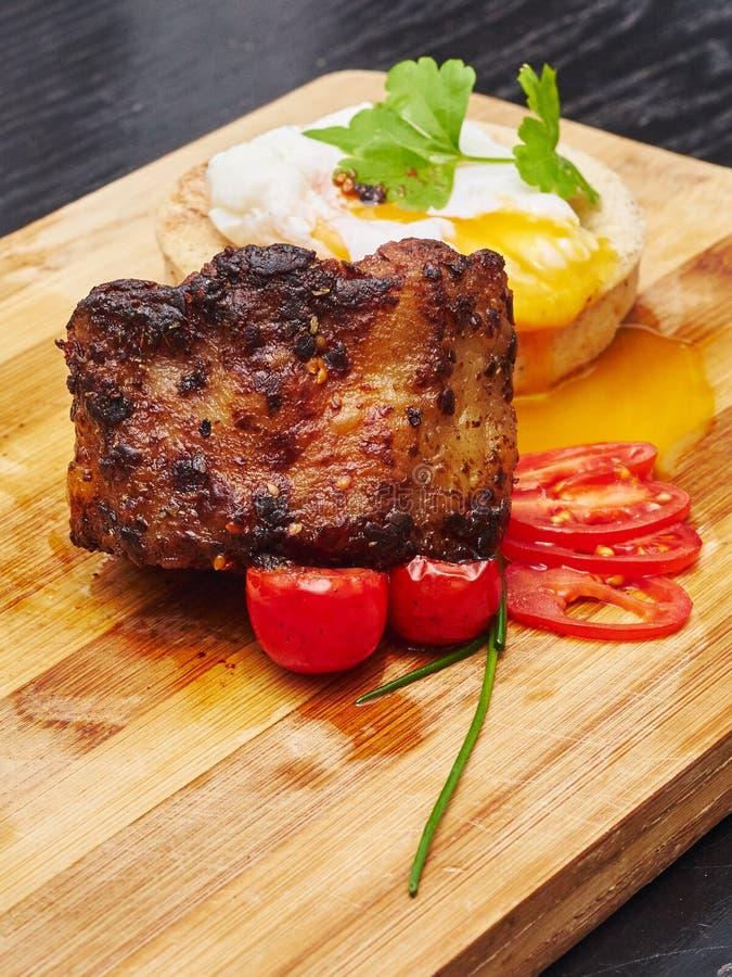 Le joint de porc a servi avec les tomators et l'oeuf de bébé sur le conseil en bois images libres de droits