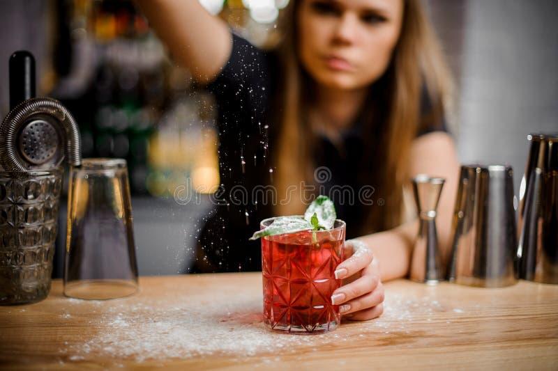 Le joli barman finit la préparation du cocktail alcoolique rose en ajoutant un amer du sucre en poudre images stock