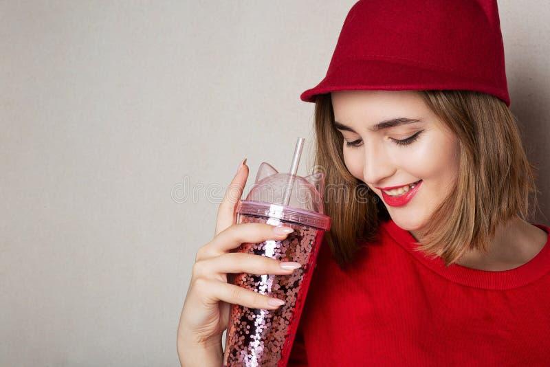 Le joli modèle de sourire utilise le chapeau rouge et le chandail, tenant le cocktail au studio L'espace pour le texte photo libre de droits