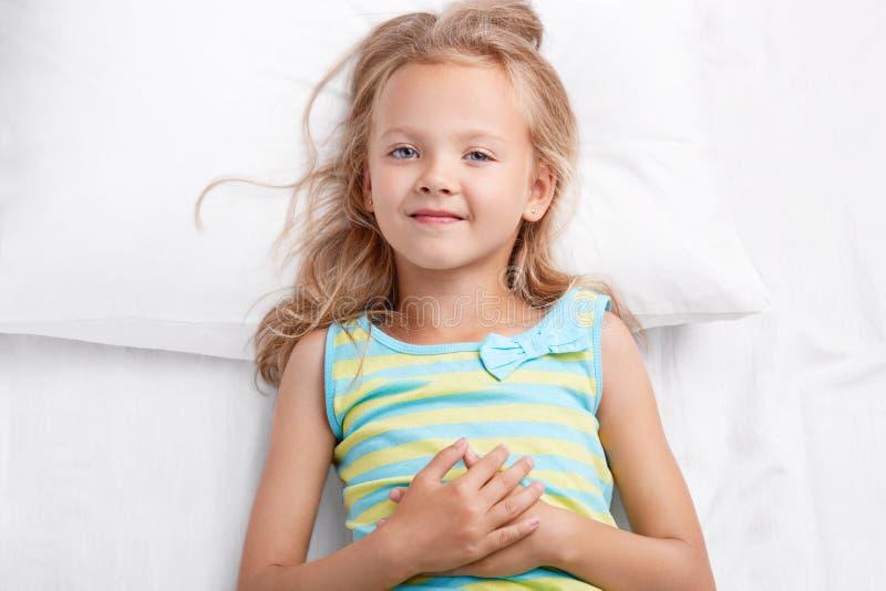 Le joli petit enfant a le regard agréable, sourire de charme, cheveux légers, yeux bleus, peau saine, maintient des mains sur l'e photographie stock libre de droits