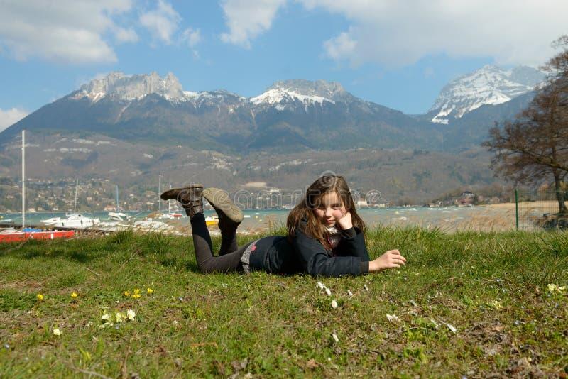 Le joli préadolescent se situe dans l'herbe verte image stock
