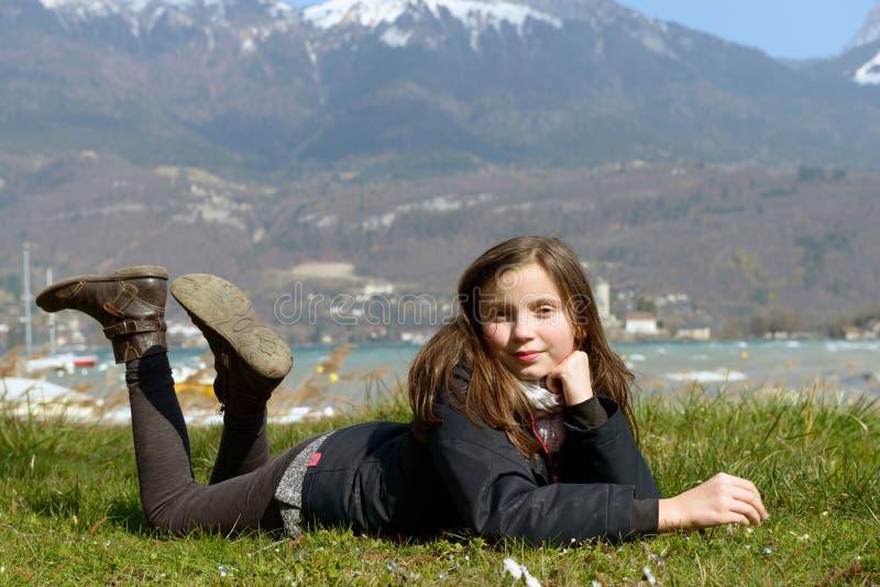 Le joli préadolescent se situe dans l'herbe verte photo libre de droits