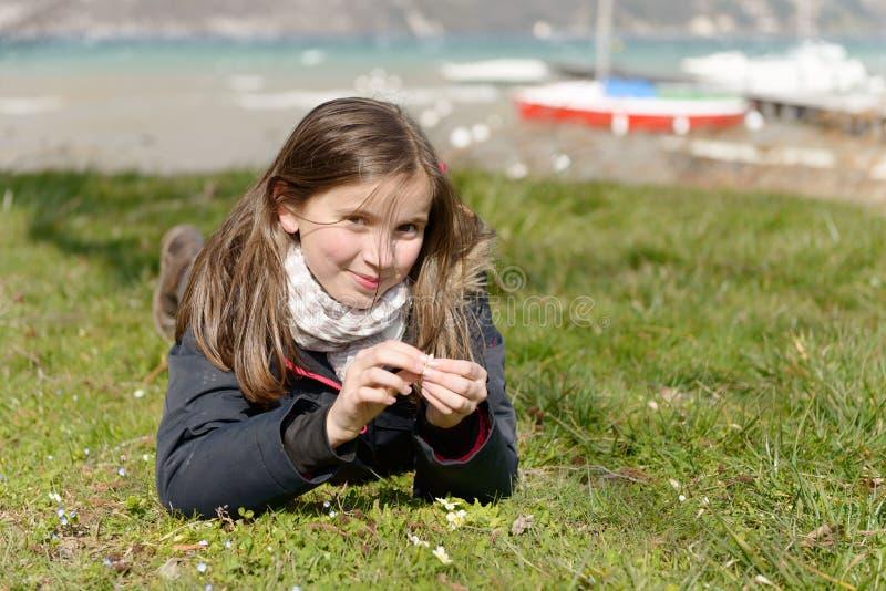 Le joli préadolescent se situe dans l'herbe verte photographie stock