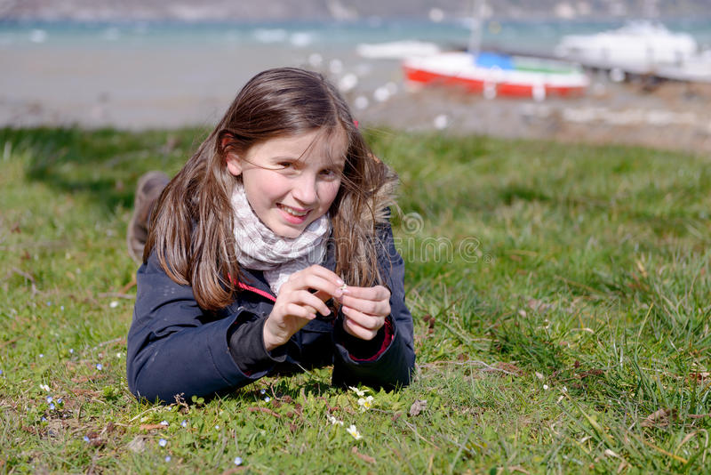 Le joli préadolescent se situe dans l'herbe verte photos stock