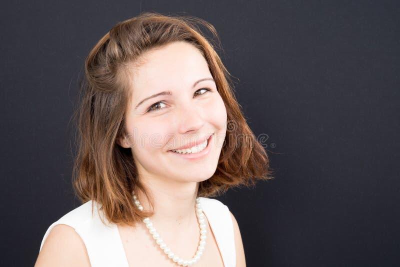 Le joli sourire de jeune femme et l'ijn heureux noircissent la beauté de fond photo stock