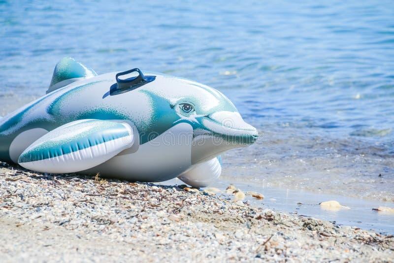 Le jouet de fantaisie de dauphin pour des enfants sur la plage, préparent pour la mer Les vacances d'été badinent des jouets Anne photo stock