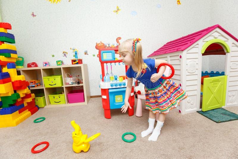 Le jouet de lancement de fille blonde assez petite sonne dans le jardin d'enfants image stock