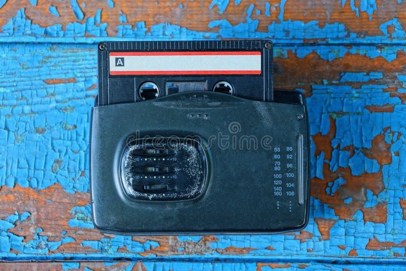Le joueur audio noir avec une cassette se trouve sur une table bleue usée image libre de droits