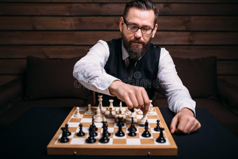 Le joueur d'échecs masculin sérieux entreprend la démarche de victoire images libres de droits