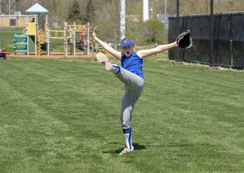 Le joueur de base-ball enthousiaste de fille avec les bras tendus et la jambe a donné un coup de pied haut image stock