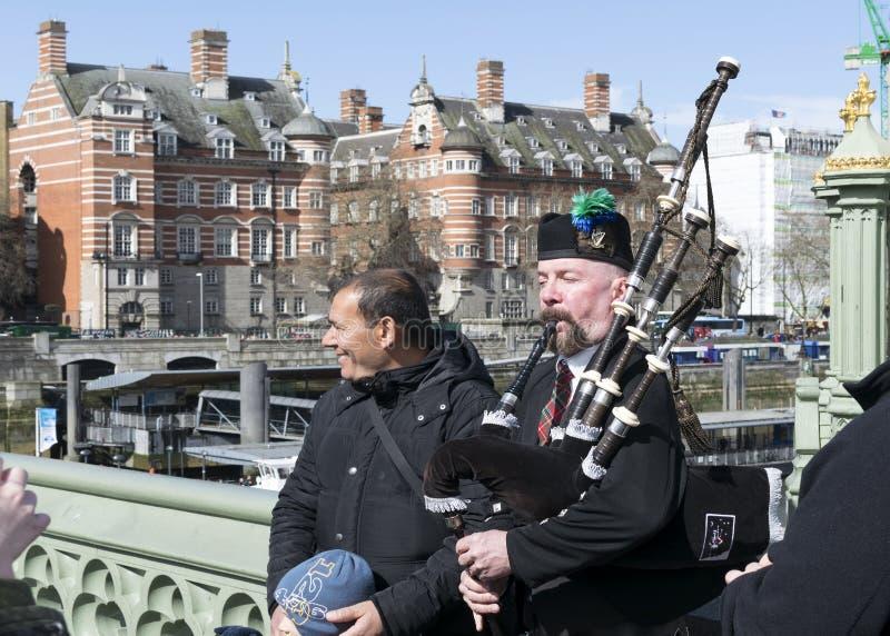 Le joueur de cornemuse exécute la musique sur le pont de Westminster, Londres, unissent image libre de droits
