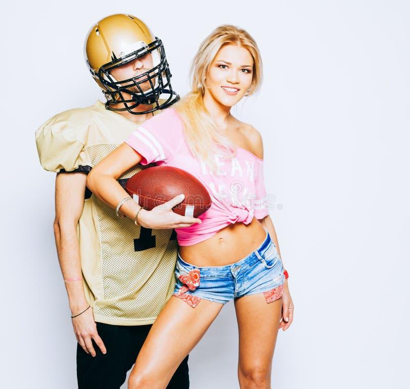 Le joueur de football américain dans l'uniforme et le casque posant avec la belle majorette blonde aux jambes longues de fille se photos stock