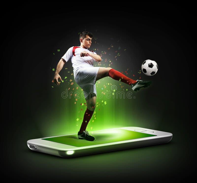 Le joueur de football dans l'action au téléphone, concept mobile du football images stock