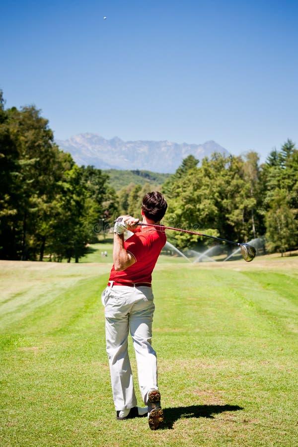 Le joueur de golf exécute un tir de pièce en t photographie stock