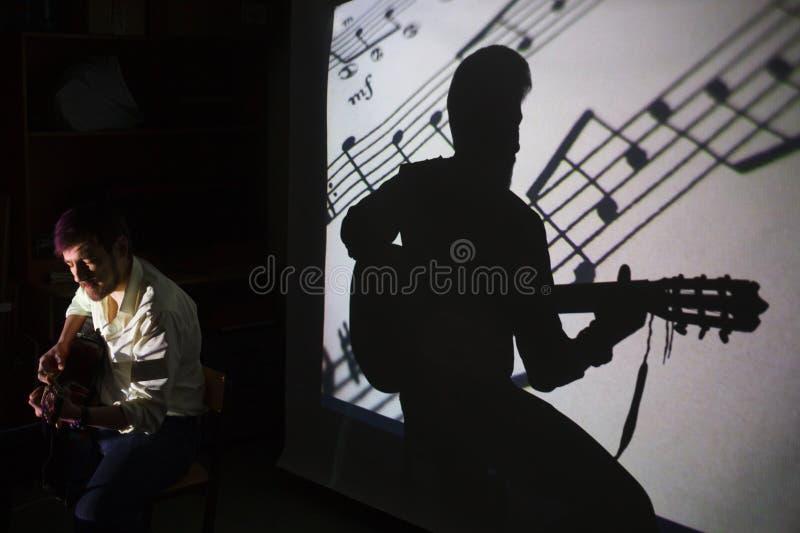 Le joueur de guitare chante la chanson avec une ombre des notes et la silhouette du guitariste sur le fond photos stock