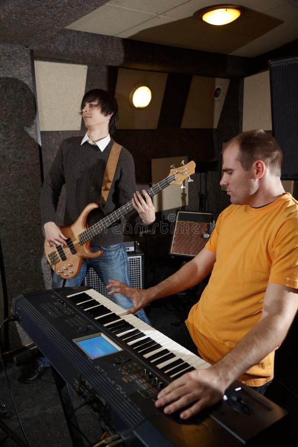 Le joueur de guitariste et de clavier travaille dans le studio photographie stock libre de droits